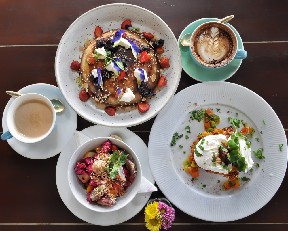 Clockwise: Skillet Buttermilk Hotcake, Cappuccino, Crispy Sweet Corn Fritters, Tropical Fruit of paradise, Chai Tea